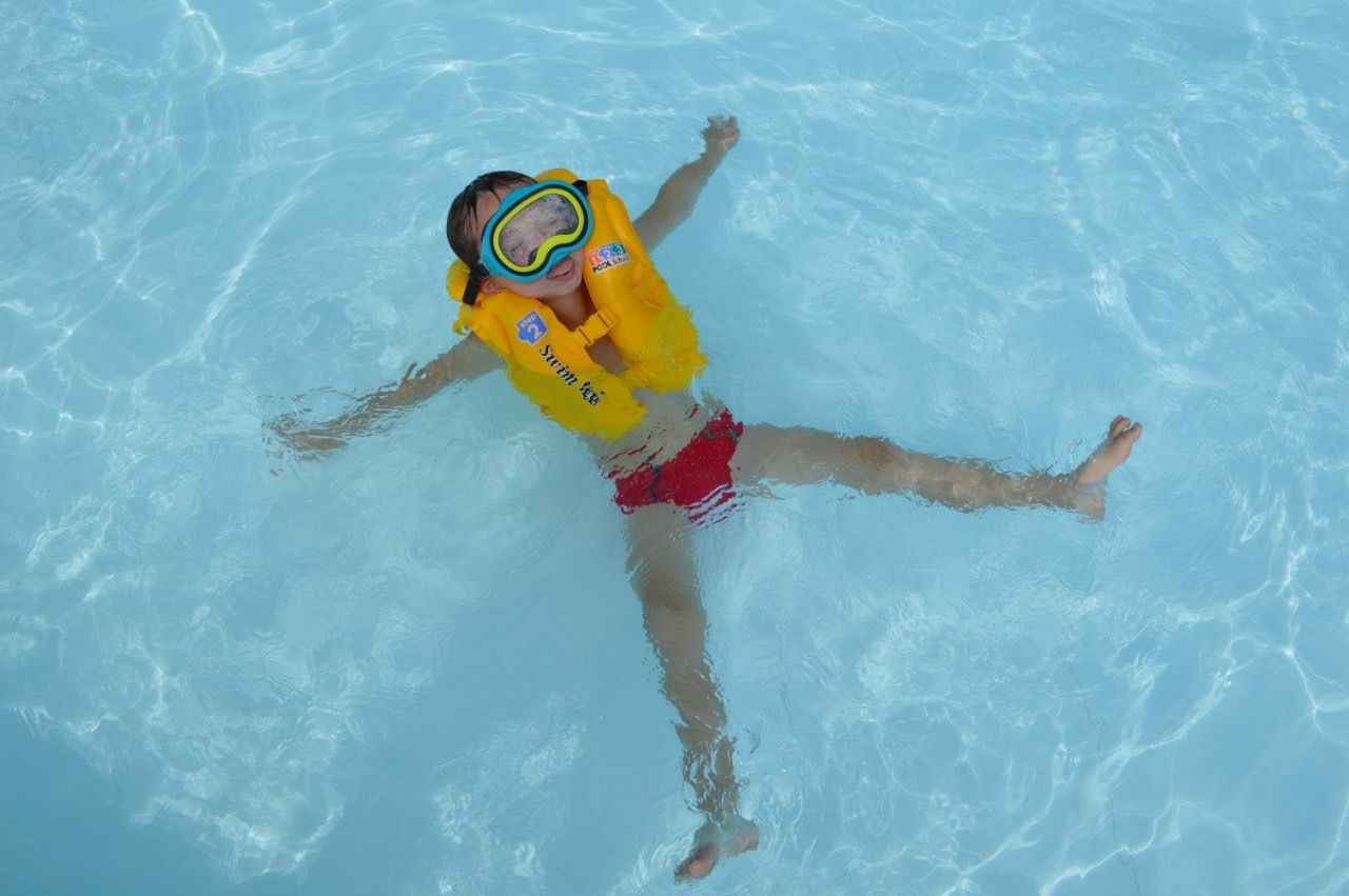 HIGH ANGLE VIEW OF BOY FLOATING IN POOL
