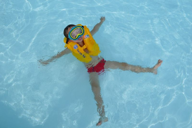 High angle view of boy floating in swimming pool