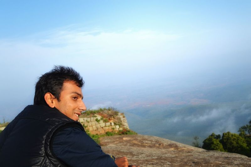 Smiling Man Looking Away On Mountain Against Sky