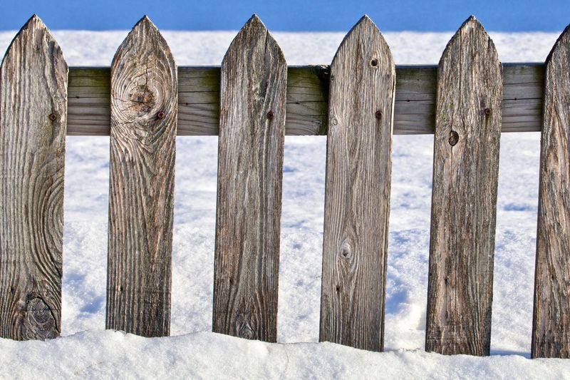 Wooden posts on fence against sky