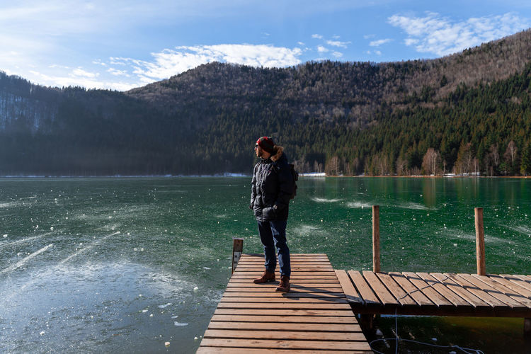 Full length of man standing on pier over lake