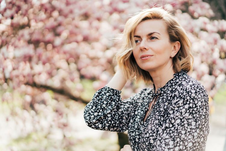 Beautiful woman looking away against cherry tree