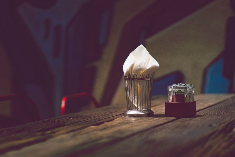 Close-up of tissue paper in container with condiment on table at restaurant