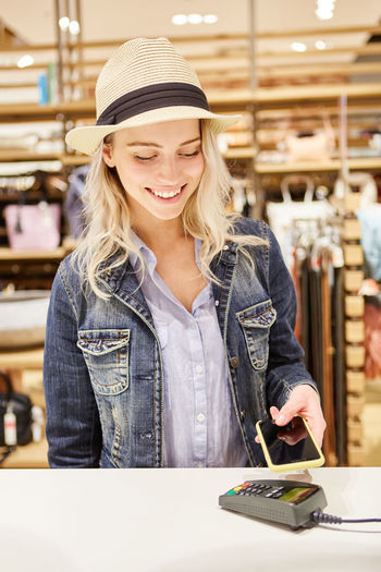 Smiling young woman making nfc payment