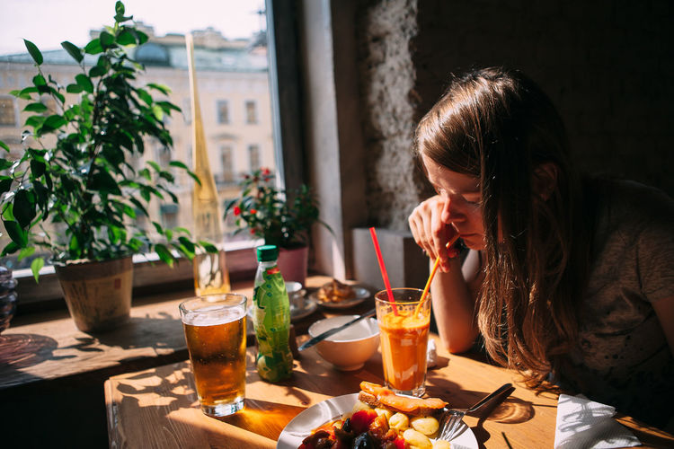 Woman Drinking a Juice Adult Alcohol Blond Hair Day Drink Drinking Glass Food Food And Drink Freshness Indoors  One Person One Young Woman Only People Real People Sitting Table Women Young Adult Young Women