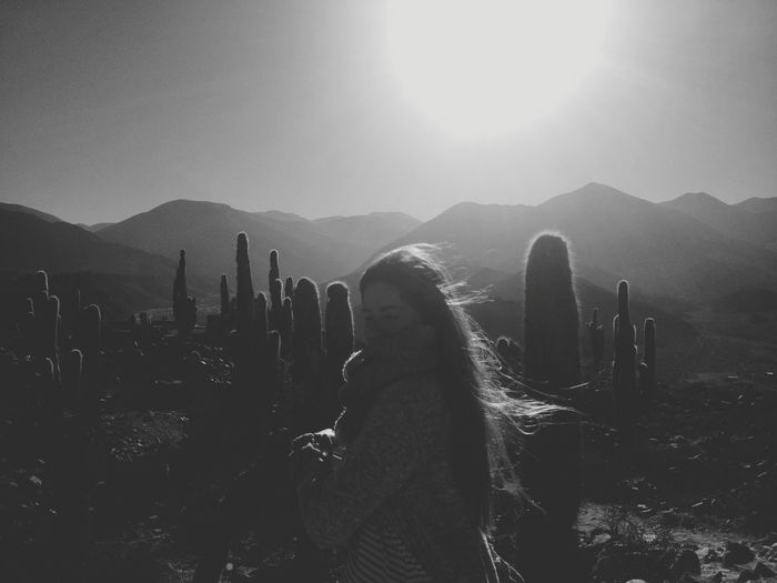Young woman standing by cactus on mountains against sky