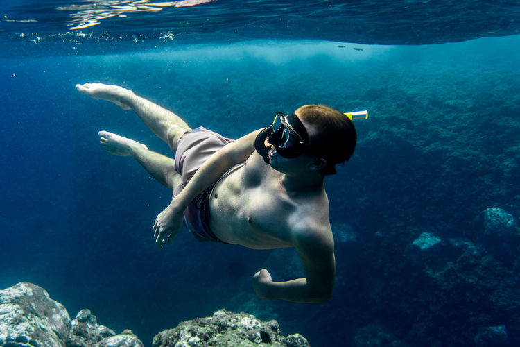 Shirtless young man snorkeling in sea