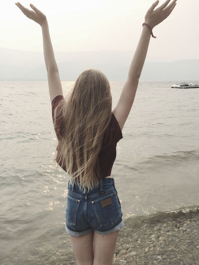 Rear view of woman standing with hands raised at beach against sky