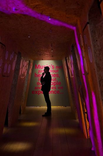 Full length rear view of woman walking in illuminated building