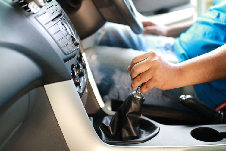 Midsection of man holding gear while driving car