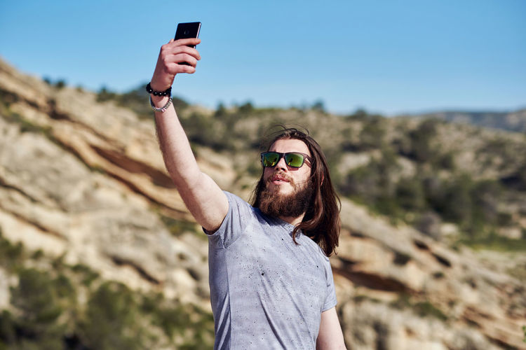 Young Man Wearing Sunglasses Talking Selfie While Standing On Mountain
