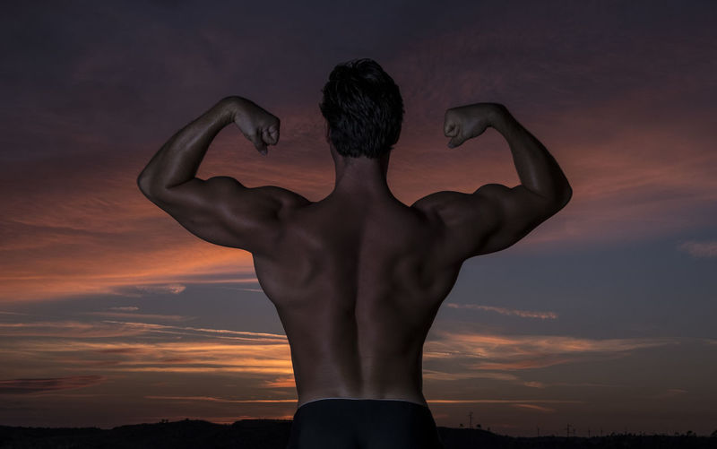 Rear View Of Shirtless Man Flexing Muscles Against Sky During Sunset
