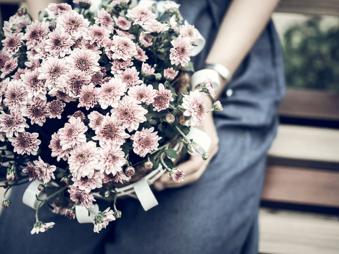 Midsection of woman holding pink flowers bouquet