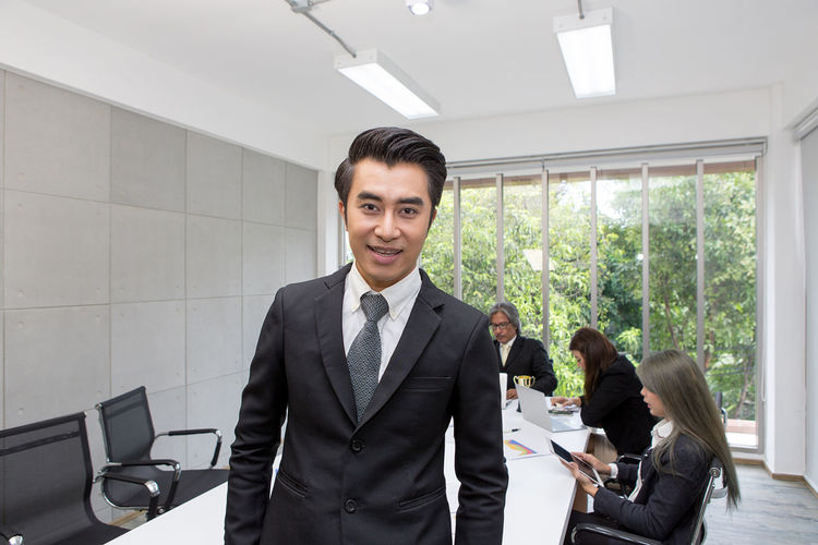 Portrait of man standing with colleagues discussing in background at office