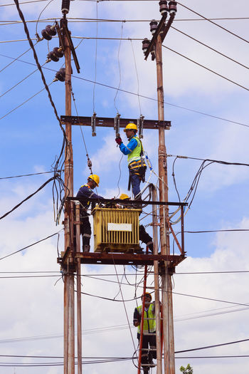 Low angle view of workers repairing cable