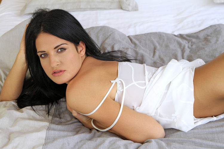 Close-Up Portrait Of Seductive Woman Lying On Bed At Home