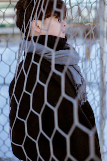 Side view of handsome young man standing by net during winter