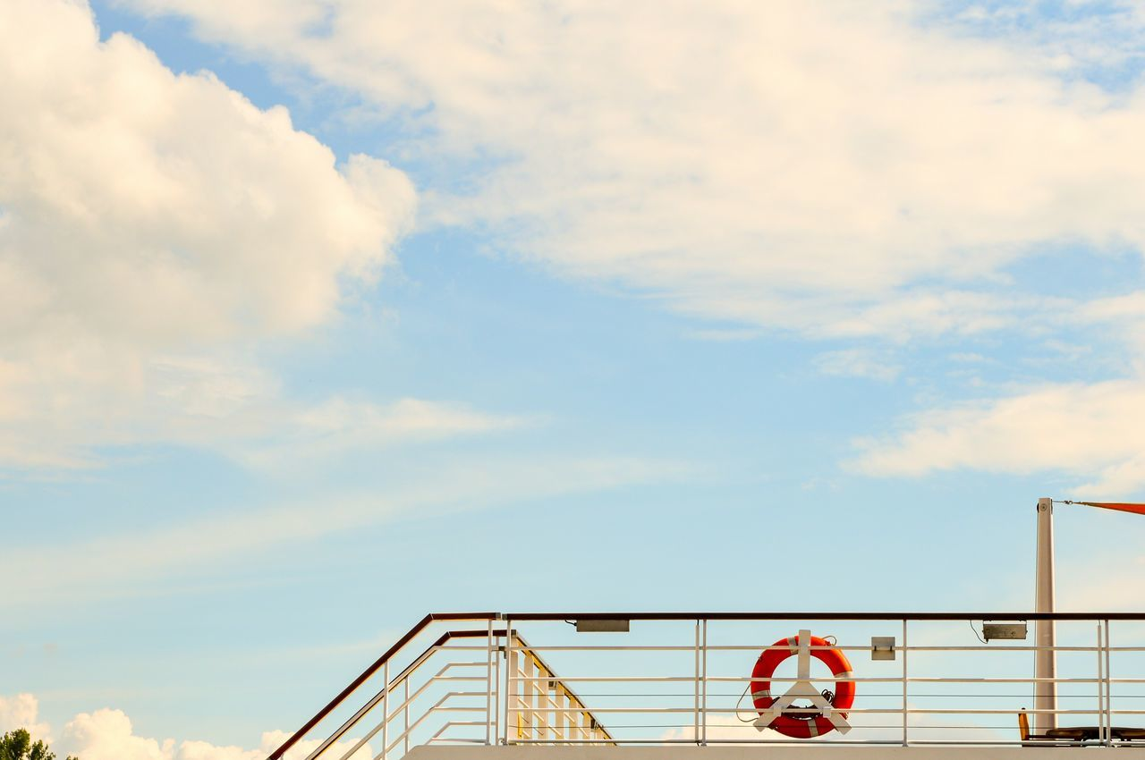 Low angle view of lifeguard ring on railing against sky