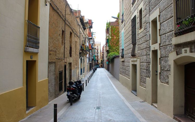 An empty Barcelona street Architecture Building Building Exterior City City Life City Street Composition Exterior Historic Leading Moped Narrow No People Perspective Residential Structure Scooter Sidewalk Street The Road Ahead The Way Forward Vanishing Point Vespa Walking