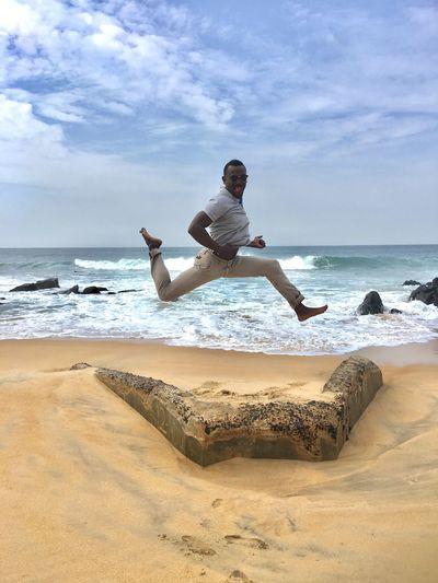 Man Jumping At Beach Against Sky