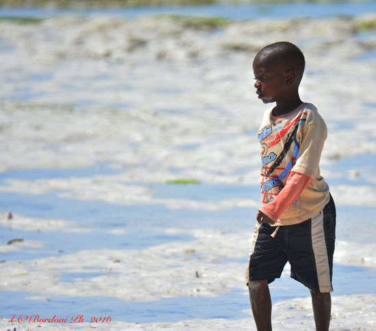 Africa Beach Beauty In Nature Casual Clothing Childhood Cute Elementary Age Focus On Foreground Full Length Girls Innocence Leisure Activity Lifestyles Ocean Sand Scenics Shore Standing Tanzania Tranquility Vacations Water Young Adult Young Boy Zanzibar