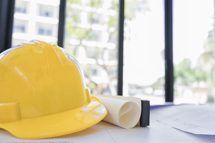 Close-up of yellow hardhat by blueprint at desk in office