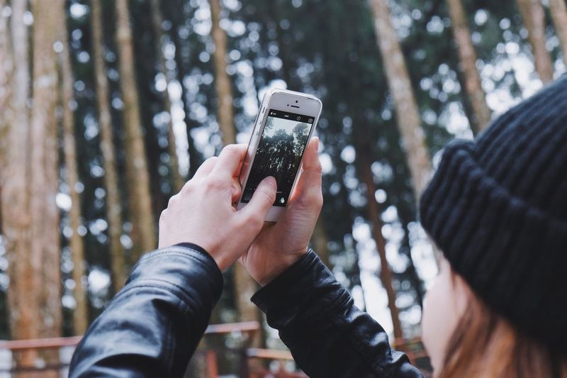 Close-up of hand holding smart phone outdoors