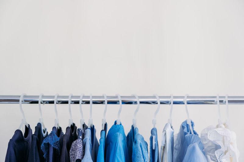 Fast fashion, sustainable fashion, minimalist wardrobe. variety of female blue clothing on hanging