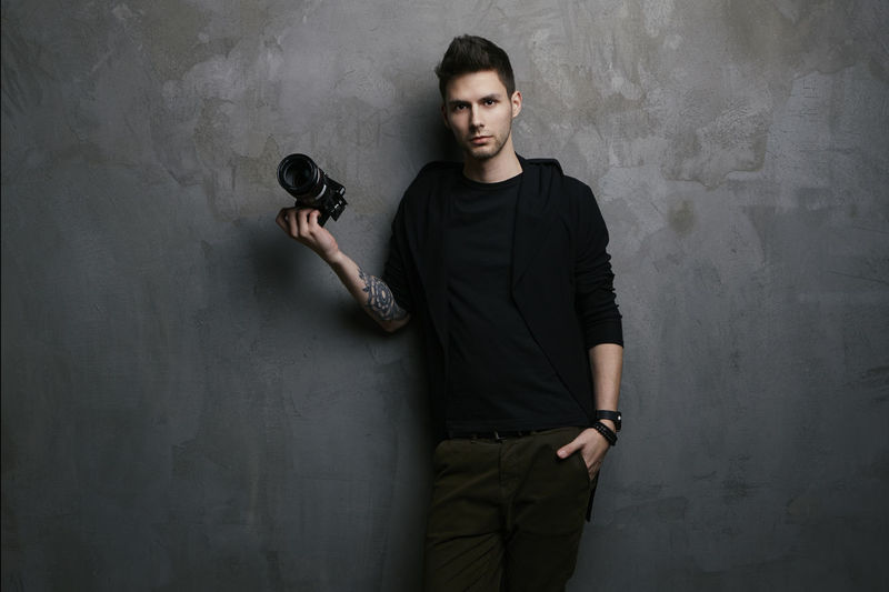 Photographer leaning against the wall Camera Wall Black Color Casual Clothing Concrete Confidence  darkness and light Front View Gray Hand Holding Indoors  Lifestyles Looking At Camera One Person Photographer Portrait Real People Standing Tattoo Three Quarter Length Wall - Building Feature Young Adult Young Men