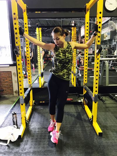 Gym Exercising Healthy Lifestyle Lifestyles Full Length Sports Clothing Exercise Equipment Indoors  Strength Real People Sports Training Mid Adult Women Health Club Wellbeing Young Women Young Adult Standing Holding Self Improvement Strength Training