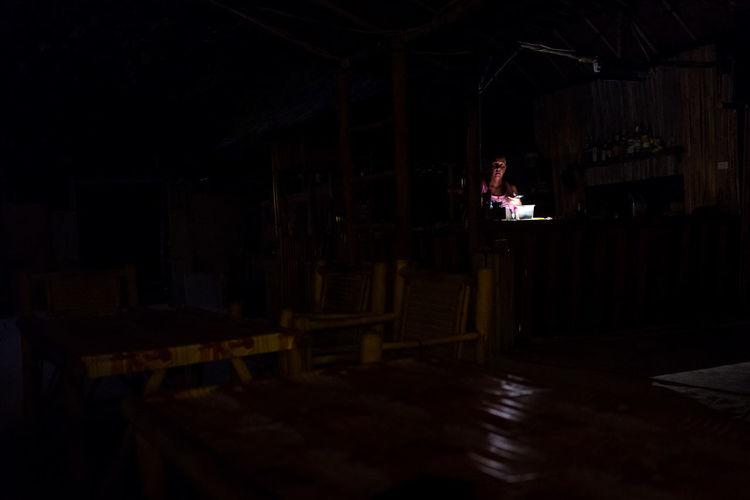Koh Lipe One Person Indoors  Real People Dark Business Lifestyles Architecture Standing Domestic Room Sitting Leisure Activity Table Activity Seat Men Night Concentration Restaurant Building