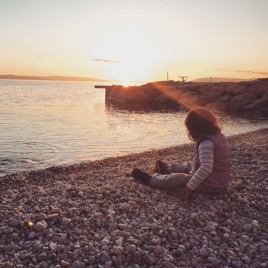 Girl Sitting On Pebbles At Sea Shore During Sunset