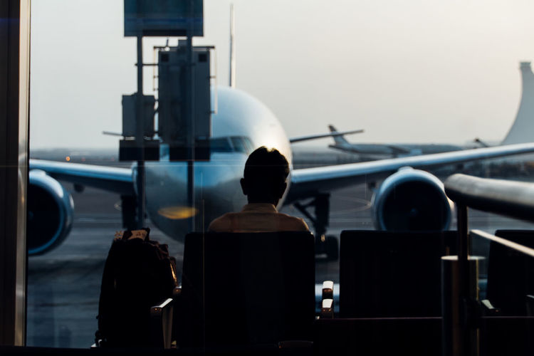 Rear View Of Man Looking At Airplane While Sitting In Airport