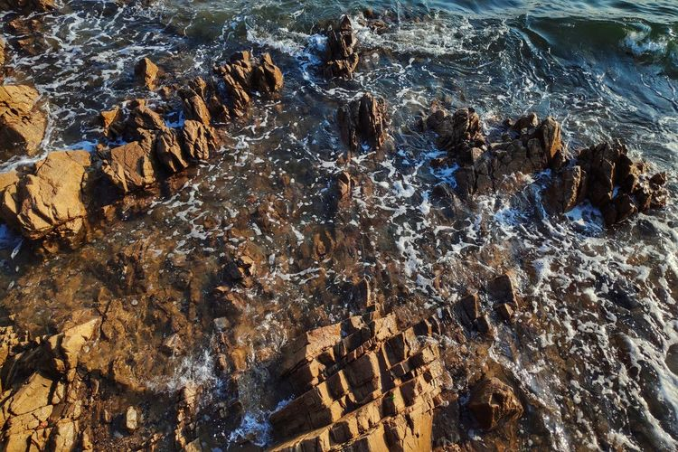 Beach Beauty In Nature Day Flowing Flowing Water High Angle View Land Motion Nature No People Outdoors Power In Nature Rock Rock - Object Rock Formation Scenics - Nature Sea Solid Stream - Flowing Water Water Waterfront