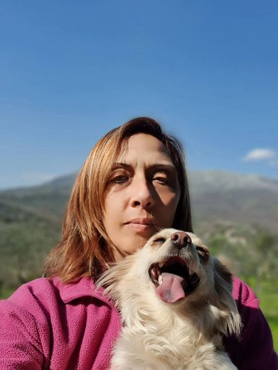 Portrait of woman with dog against sky