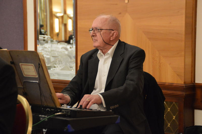 Senior man playing electric piano at event