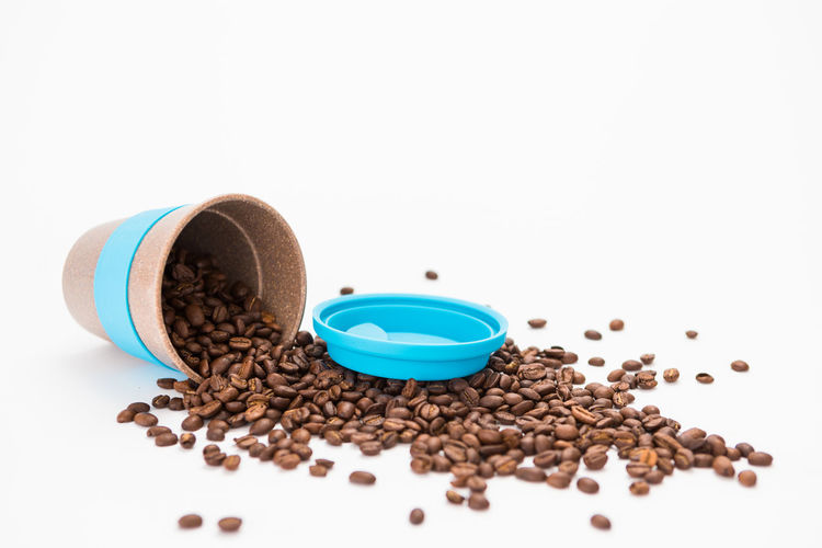 Overturned White Coffee cup with Coffee Beans Inside on a White Background White Background Studio Shot Indoors  Roasted Coffee Bean Still Life Food And Drink Coffee Coffee - Drink Freshness Food Brown Close-up Large Group Of Objects No People Copy Space Mug Cup Coffee Cup Drink Seed Caffeine