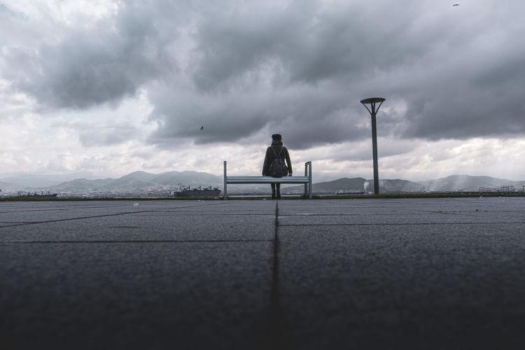 Man on street against sky