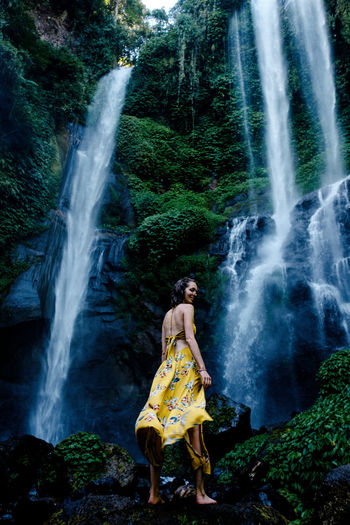 A woman in front of the Sekumpul waterfall on the island of Bali. Bali Beauty In Nature Clothing Flowing Water Forest Full Length Land Long Exposure Motion Nature One Person Outdoors Plant Scenics - Nature Sekumpul  Strength Water Waterfall Yellow Dress Young Adult Be Brave Moments Of Happiness 2018 In One Photograph Stay Out