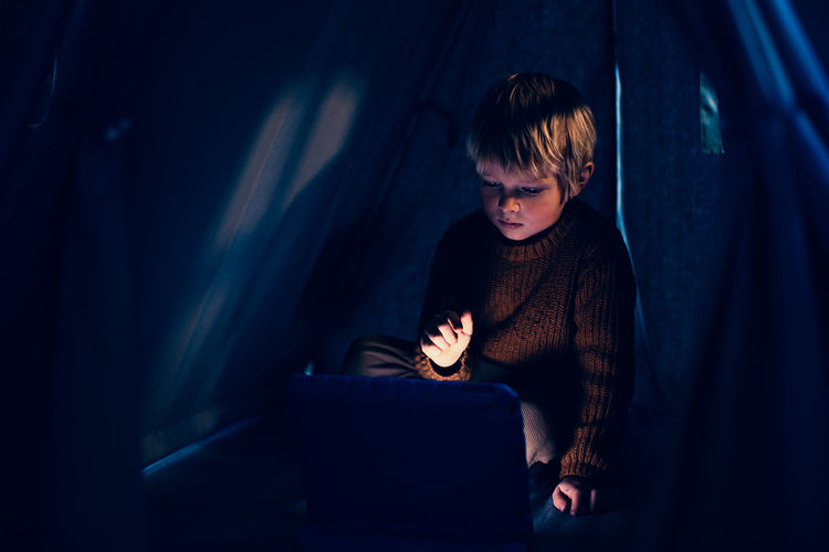 Child using touch pad at home in the tend. z generation and technology concept