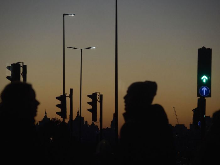 Silhouette people by stoplights against sky at night
