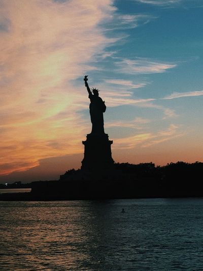 Lady Liberty EyeEmNewHere Sun Sunset Sunset Silhouettes Sunset_collection Colors New York New York City NYC Waterfront Statue Statue Of Liberty Statue Sky Water Architecture Outdoors Sculpture