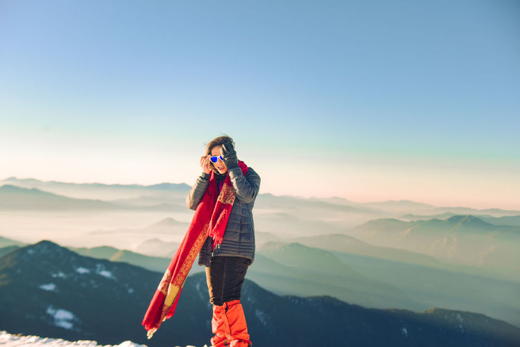 Man standing against mountain range against clear sky