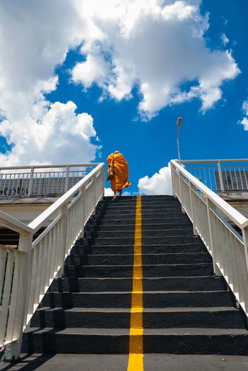 Low Angle View Of Monk Moving Up On Steps Against Sky