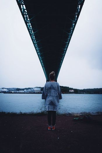 Rear view of woman standing under bridge over river against clear sky