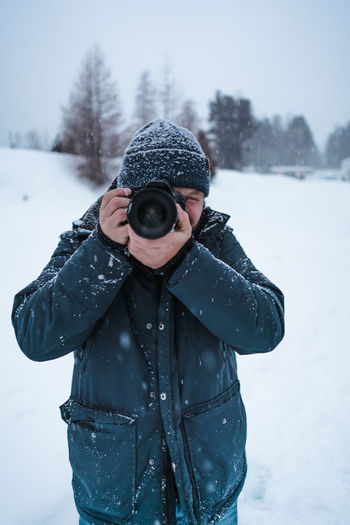 Man wearing hat standing on snow covered land