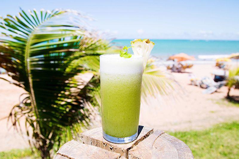 Green fruit juice on tree log at beach