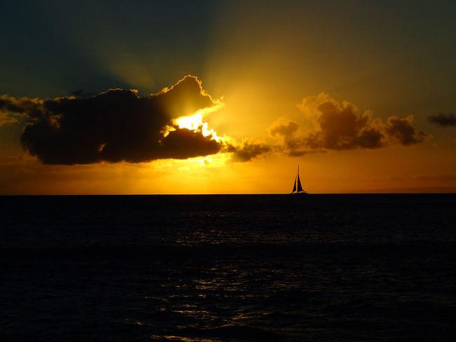Sunset Over Ocean with Rays Behind Cloud and Sailboat Silhouette on Horizon Sunset; Sailboat; Ocean; Hawaii; Tropics; Sun Rays; Rays; Light Beams; Horizon; Silhouette; Boat; Sail; Seascape; Golden; Blue; Gold; Beach; Orange; Black; Sea; Beach; Restful; Dramatic; Beautiful; Peaceful; Skyline; Sundown; Sun; Sunlight; Travel; Vacati Beauty In Nature Cloud - Sky Horizon Over Water Nature No People Outdoors Sailboat Scenics Sea Silhouette Sky Sun Sun Rays Sunset Tranquility Water Waterfront