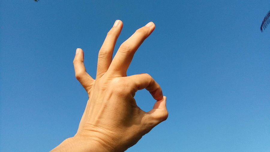 Close-up of hand showing ok sign against clear blue sky