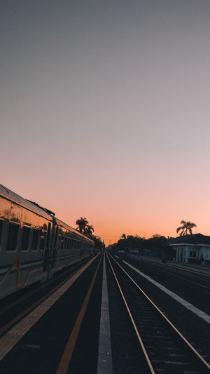 Railroad tracks against clear sky at sunset